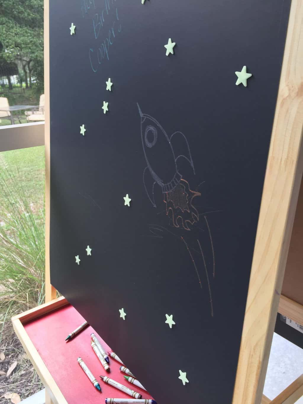 My sister put together this cute space-inspired drawing area. 1. Put black poster board over an easel or stand. 2. Draw rockets or planets with neon crayons to get the kids inspired. 3. Add glow in the dark star stickers. Major fun!